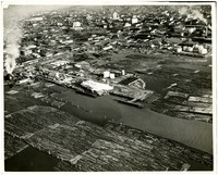 Aerial view of numerous log booms in waters of Bellingham, WA, harbor, with Bellingham in upper background