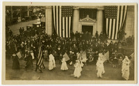 View from above of Armistice Day parade with women in white carrying American flags, marching by crowd of onlookers standing in front of imposing, columned building with two huge American flags