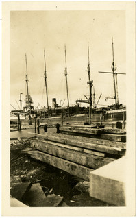 Wooden beams stacked on beach in foreground, five-masted cargo vessel docked in background