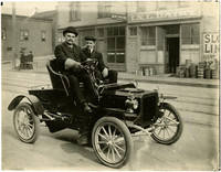 Louis De Champlian and Ralph Frizell in small, early-model automobile