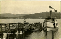 Several early-model automobiles ascend the ramp from Deception Pass ferry dock with moored passenger ferry