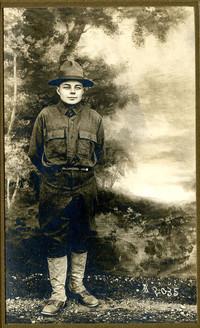 Teenage boy in junior ranger or soldier uniform poses before painted backdrop