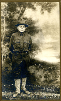 Teenage boy in junior ranger or soldier uniform poses before painted backdrop