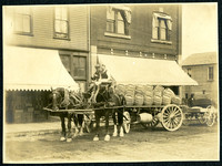 A wagon drawn by two work horses containing nineteen round wooden kegs, possibly of beer, with two unidentified men seated at the front, with several commercial buildings in the background