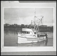 """The fishing boat """"Martle"""" in Bellingham Bay heading out from shore with Eldridge Avenue in the background"""