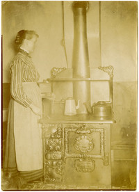 Gerda Roman holding coffee grinder stands next to wood-burning stove