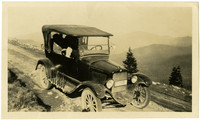 Early-model car on dirt road high above forested valley below