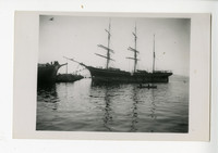 Portside view of three-masted sailing vessel near dock where people await, with two rowboats in water