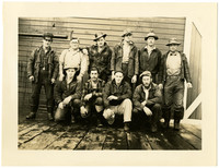 Ten men in work clothes pose in two rows on dock outside warehouse