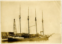Four-masted lumber schooner is moored adjacent to dock piled with lumber