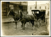 A man sits in a covered buggy hitched to two horses on a commercial street