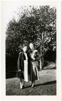 Two women pose arm in arm on lawn with trees in background