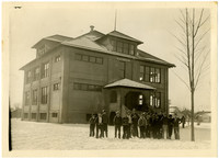 Group of students bundled for winter stand in front of an imposing three-story school house on a snowy day
