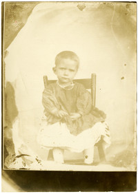 Toddler girl sits in chair for portrait
