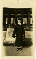 Unidentified woman posed in a cap and gown in front of the Old University of Washington Forrestry Building