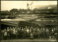 Group of nearly forty men standing next to railroad tracks with a large shute and the side of a wooden building behind them, with separate photograph attached above