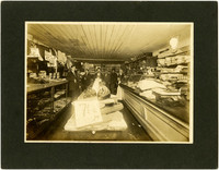 Interior of mercantile with several men standing between counters among goods