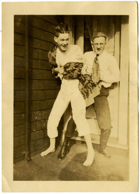 Jovial scene of two young men wrestling on front stoop