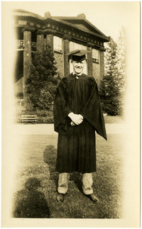 Unidentified man posed in a cap and gown in front of the Old University of Washington Forestry Building