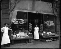 Front view of fruit store with man and woman wearing white aprons standing in front of store beside tables of fruit on display.