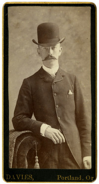 Formal studio portrait of man in suit and tophat