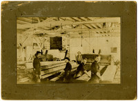 Five unidentified men paused at their work  among boards and slabs of lumber inside a lumber mill for photograph