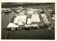 Aerial view of part of Bellingham, WA, industrial waterfront with cold-storage warehouses, fuel tanks, moored vessels, and houses along Eldridge avenue on bluff at top