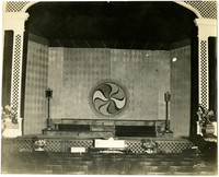 Interior of theater with organ console in front of set stage