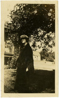 Young woman poses in fur coat under a tree