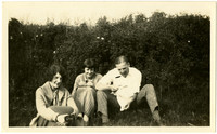Two women and a man sit on the ground in front of bushes