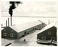 Dock with two long (cannery?) buildings with rowboats and double ender boats stored adjacent
