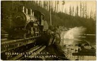 Postcard photograph of Lake Whatcom Logging Company's ALCO No. 1 engine on lakeside tracks  with a long train of lumber cars as the logs begin splashing into the lake