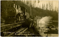 Postcard photograph of Lake Whatcom Logging Company's ALCO No. 1 engine on lakeside tracks  with a long train of lumber cars as the logs begin splashing into the lake