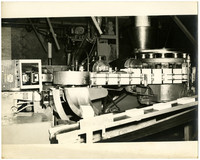 A machine in a food processing plant or cannery, likely a box former