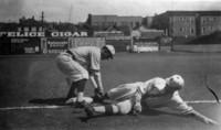 Baseball player sliding into base with baseman stooping to make the tag