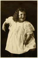 Toddler in long white dress, ringlet curls poses with black background in studio portrait