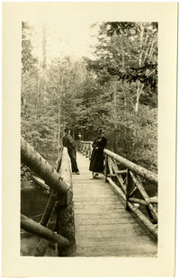 A man and woman pose mid-span on wooden bridge over river