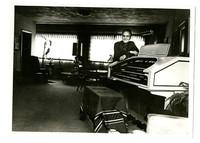 Man poses next to electric organ