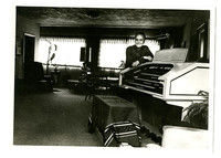 Man poses next to electric organ