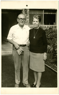 Couple - possibly Stanley Tarrant and his wife - standing close together in front of a house.