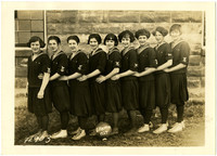 Nine girls in athletic uniforms pose with a soccer or volleyball labeled