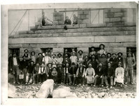 Large group of workmen and stonecutters and one small boy pose in front of Whatcom County Courthouse under construction, with blocks of stone in foreground