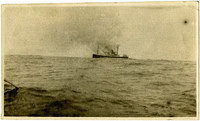 View on horizon of a cannery ship billowing smoke from onboard fire
