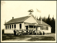 Several dozen school children and their teachers pose outside a schoolhouse with belltower and flag pole