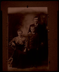 Unidentified man and boy pose with seated woman