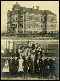 Double print shows exterior of large three story Sehome School, and image below of a group of schoolchildren posed on steps of school