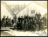 Group of about forty men standing in front of two unidentified vertical board buildings
