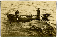 Two men guide a canoe to net fish