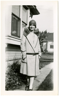 Woman in fur-collared coat poses on sidewalk outside residence