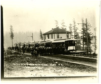 A large crowd of men and boys stand next to seven trolleys parked at a depot, with forested shore of Lake Whatcom in background